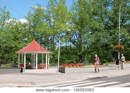 IMATRA, FINLAND - JULY 2, 2016: People go on roller skates near pavilion not far from Water supply canal on The Vuoksi River