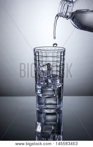 Starting to pour water into glass. Water being poured from a bottle into a glass of ice.