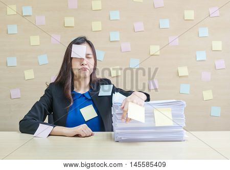 Closeup working woman are bored and tired from pile of work paper in front of her in hard work concept on blurred wooden desk and wooden wall textured background in the meeting room