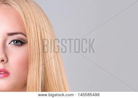 Half-face portrait of beautiful sensitive woman on gray background. copy space. Beauty Woman face Portrait.