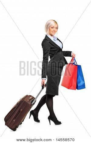 Full Length Portrait Of A Woman Carrying A Suitcase And Shopping Bags