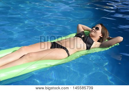 young happy beautiful woman in bikini and sunglasses lying relax on float airbed at vacation hotel resort swimming pool in Summer enjoying holidays having sunbath with tan body