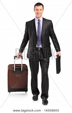 Full Length Portrait Of A Business Traveler Carrying A Suitcase