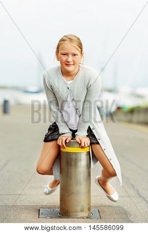 Outdoor portrait of a cute little 9-10 year old girl, wearing knitted long grey cardigan