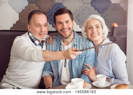 Elated atmosphere. Joyful smiling senior couple and their adult son sitting at the table and making selfies while resting in the cafe