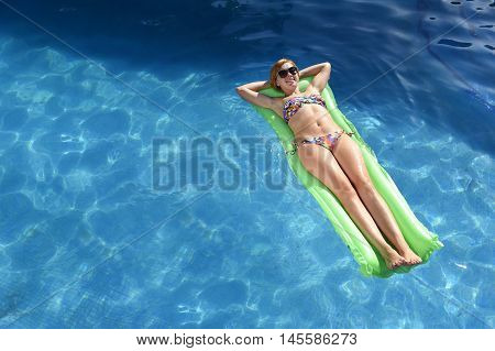 young happy beautiful woman in bikini and sunglasses lying relax on float airbed at vacation hotel resort swimming pool in Summer enjoying holidays having sunbath with copy space for text