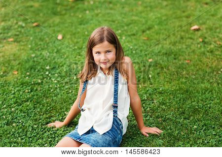 Portrait of a cute little girl 7-8 year old in the park, sitting on grass