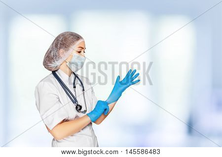 Medical surgeon doctor woman over blue clinic background. Doctor putting on sterile gloves. Place for medical advertise, medical advertising concept.