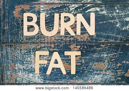 Burn fat written with wooden letters on rustic surface