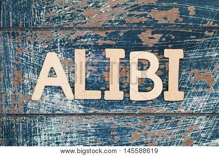 Word alibi written with wooden letters on rustic surface