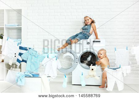little helpers funny kids happy sister and brother in the laundry to wash clothes playing and laughing