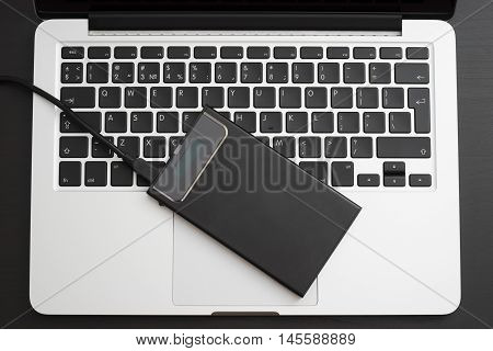 External hard disk over laptop keyboard, close-up