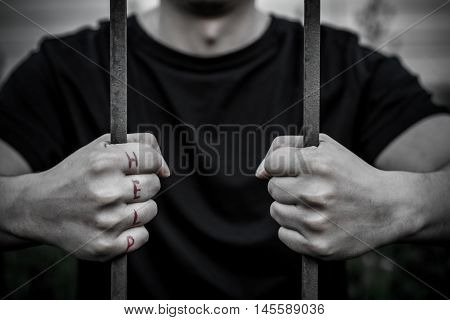 Man held with two hands for metal bars. On the fingers of one hand is written