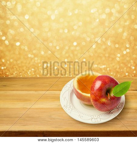 Apple with honey on wooden table over golden bokeh background. Jewish New Year holiday Rosh Hashanah concept