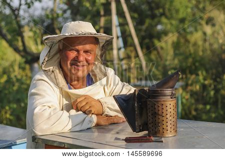 portrait of a beekeeper on apiary at hive with bees.