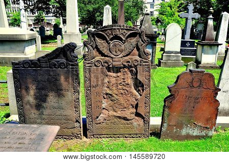 New Haven Connecticut - June 19 2013: Three 18th century sandstone tombstones with angel figures in historic Grove Street cemetery