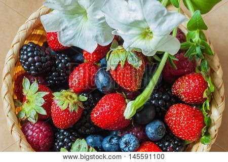 Organic berries with its own rustic garden in a wicker bowl, top view, decorated with flower, blueberries, strawberries, raspberries and blackberries. Healthy, detox superfood concept.