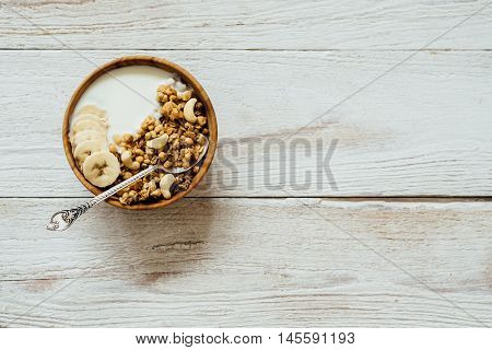 Homemade Oatmeal Granola With Yogurt In Wooden Bowl