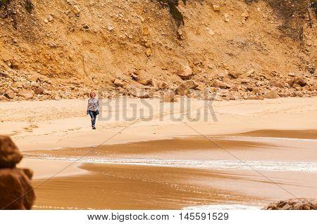 Female traveler walking on the isolated beach Ursa on Atlantic coast near the Cape Roca, Sintra, Portugal