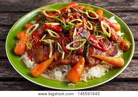 takeawy classic pork on rice with fried in sticky souce carrots, sprinkle of chillie and spring onion.
