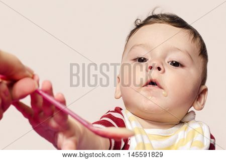 Mother hand feeding infant baby food. Child trying to grab the spoon.  Six month old beginning food diversification. Cute baby boy eating food with the spoon.