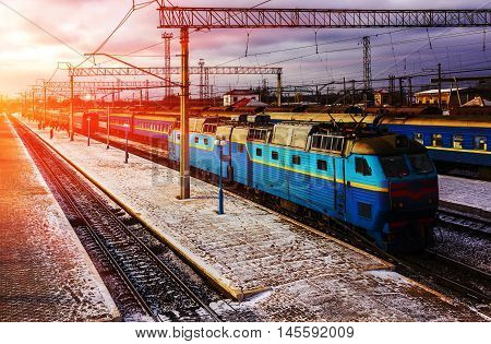 blue train with railcars at the platform at sunset