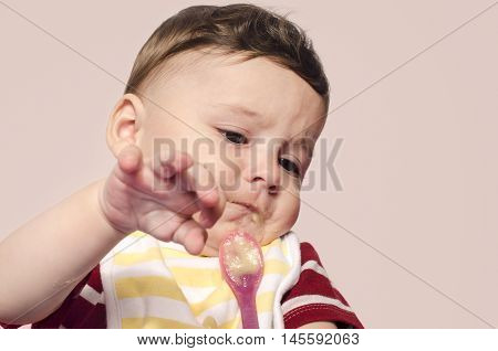 Cute baby refusing to eat baby food from the spoon. Six month old beginning food diversification. Little child cringing and pushing the spoon with food.