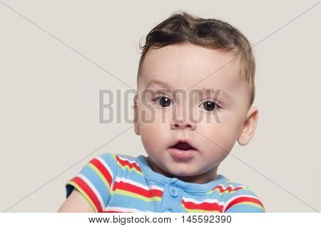 Portrait of a cute curious baby boy sitting down. Adorable six month old child happy looking surprised raising his eyebrow.