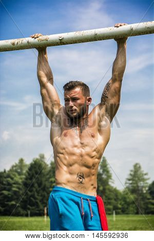 Portrait of tattooed topless sportsman doing abs exercise on metal railing outdoor in city park