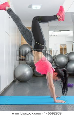 Young Woman Trying Handstand At The Gym