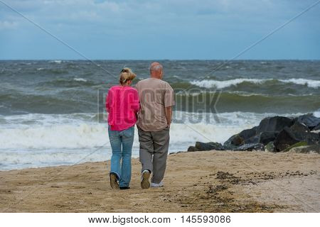 Spring Lake NJ US -- Sept 3 2016. A couple walks on the beach before an impending storm while the ocean churning. Editorial Use Only.