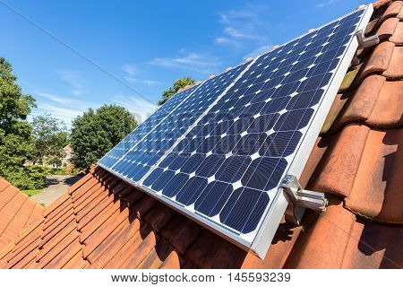 Row of blue solar panels on orange roof