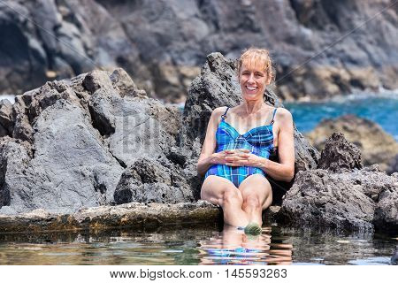 Dutch woman sunbathing on rocks at natural sea fwater