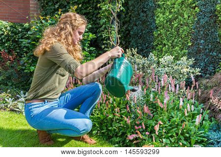 Young caucasian woman with watering can above flowers
