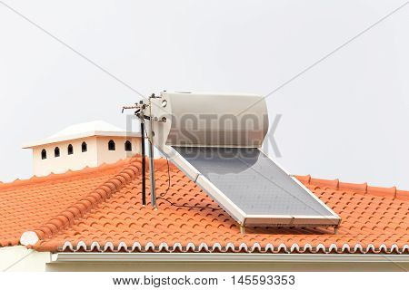 Hot water boiler with solar panel on roof of house