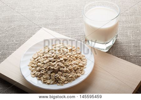 Saucer With Dry Cereal On A Wooden Board And A Glass Of Milk