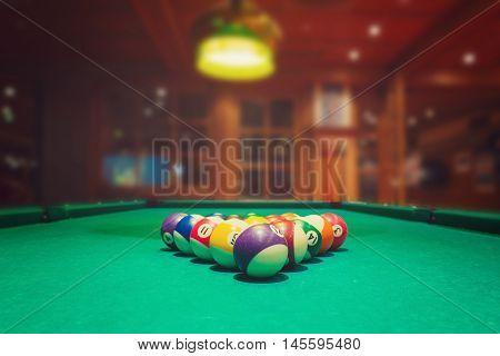 Billiard balls on green pool table in bar or pub