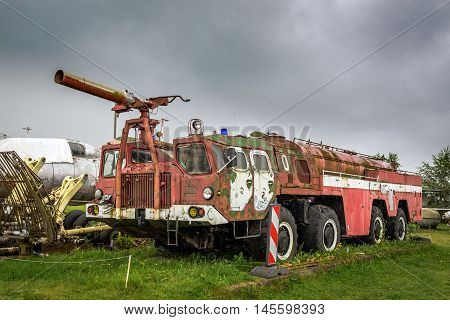 Old abandoned airport firetruck on a green field