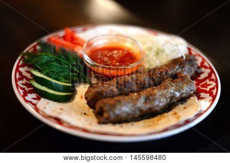 Uzbek kebab on a plate with vegetables