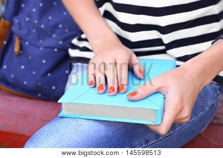 Woman holding book and sitting on bench in park