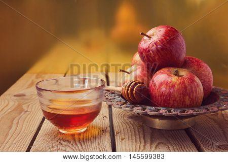 Apple and honey over golden background. Jewish Rosh hashana (new year) celebration