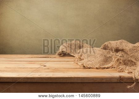 Vintage background with wooden table and sackcloth