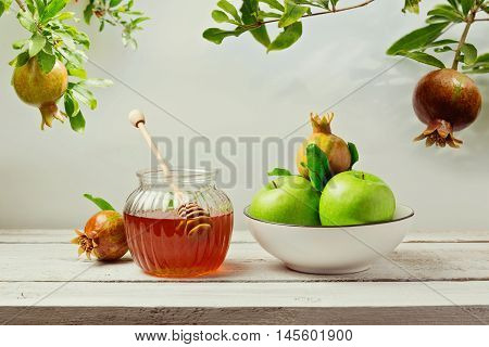 Jewish holiday Rosh Hashana (new year) background with honey jar apples and pomegranate tree