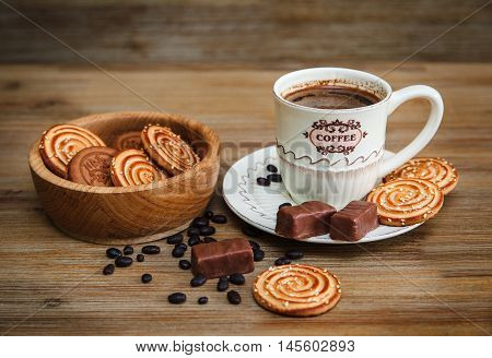 There are Cookies,Candy,Chocolate Peas,Poppy;Porcelain Saucer and Cap with Coffe,Tasty Sweet Food on the Wooden Background