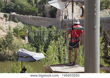 Zip line attraction beside Saint Martin bridge over Tagus river Toledo Spain