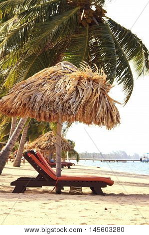 Relaxing setup of chairs and a tiki hut on a beautiful beach in Belize