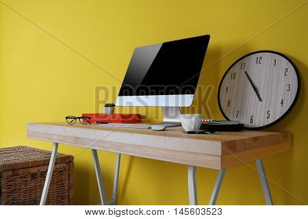 Working place on yellow wall background