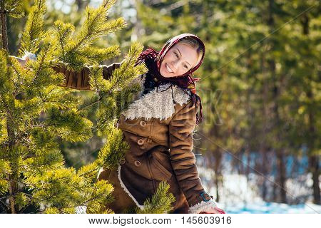 Young nice blond woman hold pine branches. Girl clothed shawl and sheepskin coat. Sunny winter day. Russian national suit.
