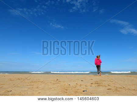 Girl on windy beach with pink jumper