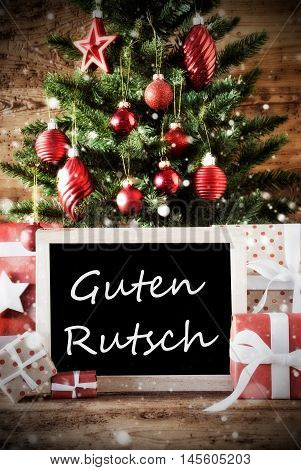 Christmas Card For Seasons Greetings. Christmas Tree With Balls. Gifts Or Presents In The Front Of Wooden Background. Chalkboard With German Text Guten Rutsch Means Happy New Year
